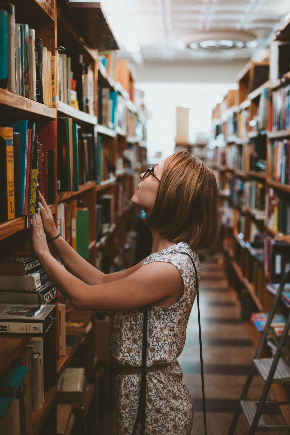 Decorative photo of a woman looking up at a high shelf of books in a library